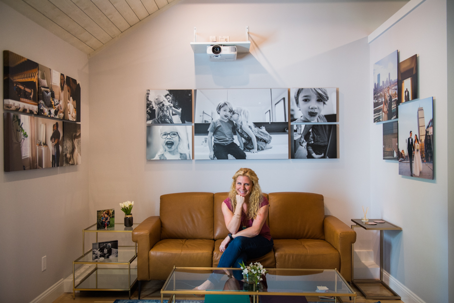 Portrait photographer sits on a couch in her photography studio in Wayland Massachusetts