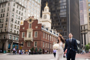 A bride and groom walk down a busy street in Boston Massachusetts.